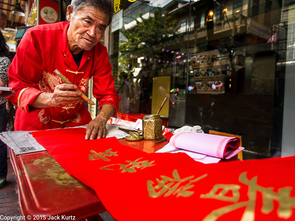 """17 FEBRUARY 2015 - BANGKOK, THAILAND: A calligrapher writes out Chinese New Year's greetings for customers Charoen Krung Road in Chinatown in Bangkok. Chinese New Year is February 19 in 2015. It marks the beginning of the Year of Sheep. The Sheep is the eighth sign in Chinese astrology and the number """"8"""" is considered to be a very lucky number. It symbolizes wisdom, fortune and prosperity. Ethnic Chinese make up nearly 15% of the Thai population. Chinese New Year (also called Tet or Lunar New Year) is widely celebrated in Thailand, especially in urban areas like Bangkok, Chiang Mai and Hat Yai that have large Chinese populations.       PHOTO BY JACK KURTZ"""