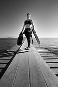 Femme sur un ponton tenant des palmes de nage à la main. Photographie en Noir et Blanc