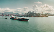 E.R. Martinique container ship motors through the Hong Kong harbour with a tug boat by it's side.