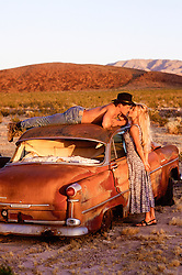sexy couple having fun around around an old abandoned car in the California Desert