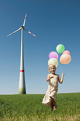 Girl running with bunch of balloons in windfarm, Bavaria, Germany