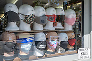 Coronavirus pandemic masks and face coverings are on display in the window of a corner shop in Whitechapel, on 29th July 2020, in London, England.
