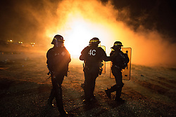 "© Licensed to London News Pictures . 23/10/2016 . Calais , France . Riot police charge residents at the Calais migrant camp known as "" The Jungle "" , in Northern France , on the evening before the start of the eviction and destruction of the camp . Photo credit: Joel Goodman/LNP"
