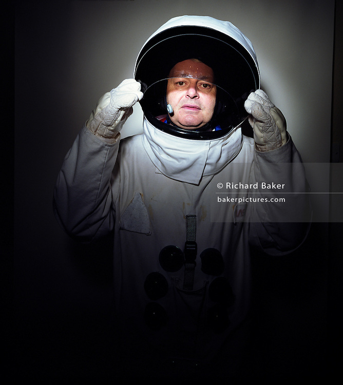 A portrait of space-suited frequent flyer astronaut Alan Watts in his north London home, England. Alan, 51, runs an electrical company and qualified for a free space space flight after being contacted by Sir Richard Branson's Virgin Galactic space company, having accumulated 2 million air miles on the Virgin Atlantic flight network. Aboard the re-usable space vehicle will be 6 passengers, each of whom will have paid $200,000 for the 40 minute flight to 360,000 feet (109.73km, or 68.18 miles) and to experience just 6 minutes of weighlessness. Flights start around 2009/10 from a Mojave desert test facility but therafter, at the new Philippe Starck-designed SpacePort America, New Mexico, USA. a 27 square mile, $225 million headquarters and mission control facility near Las Cruces.  ....