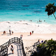 People swimming in the small surf of the Caribbean Sea from one of the beautiful white, sandy beaches next to the Maya civilizations ruins of Tulum on the eastern coast of Mexico's Yucatan Peninsula. In the foreground is party of the stairs from the archeological site down to the beach below.