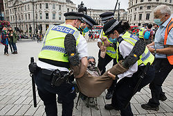 London, UK. 3rd September, 2020. Metropolitan Police officers arrest a climate activist from Extinction Rebellion in Trafalgar Square during a 'Carnival of Corruption' protest against the government's facilitation and funding of the fossil fuel industry. Extinction Rebellion activists are attending a series of September Rebellion protests around the UK to call on politicians to back the Climate and Ecological Emergency Bill (CEE Bill) which requires, among other measures, a serious plan to deal with the UK's share of emissions and to halt critical rises in global temperatures and for ordinary people to be involved in future environmental planning by means of a Citizens' Assembly.
