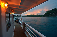 A small passenger ship pulls into a bay at sunrise in Manuel Antonio National Park, one of the smallest and most visited parks in Costa Rica.