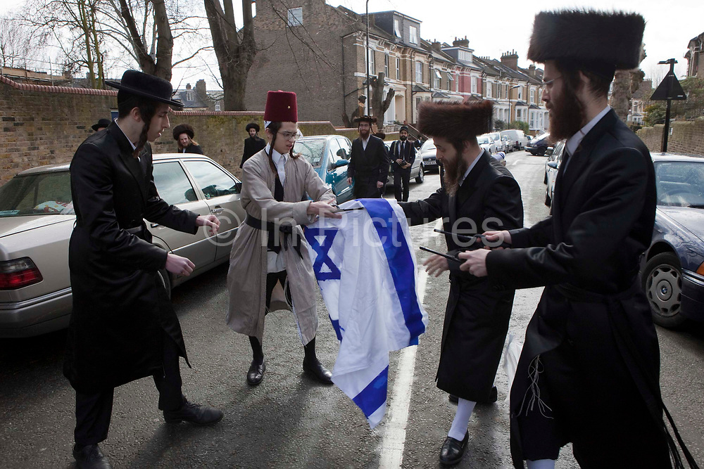 Members of the Ultra Orthodox Jewish anti-Zionist group, the Neturei Karta, burning the Israeli flag in the street outside their synagogue during the festival of Purim.  Stamford Hill, London, United Kingdom.