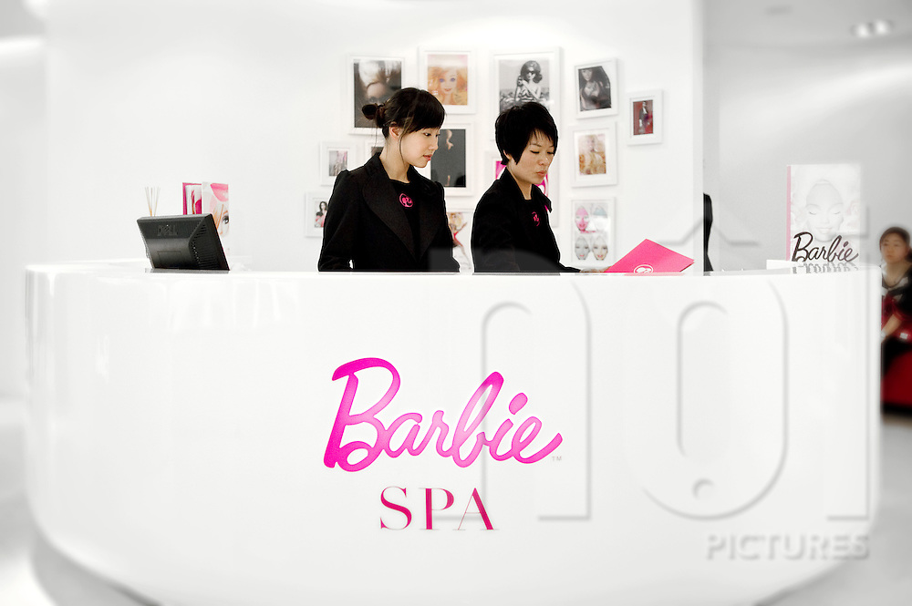 Two chinese receptionists stand behind a desk in Barbie shop's spa. Shanghai, China, Asia.