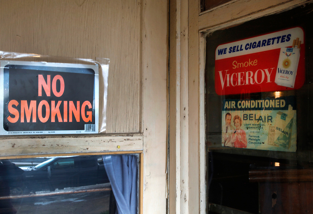"""Old signs advertising cigarettes next to a new sign reading """"no smoking"""" are seen at entrance to the tavern in the village of Monowi, Nebraska April 27, 2011. Elsie Eiler, who runs the tavern, is the sole person living in Monowi making it the only incorporated town, village or city in the United States with just one resident.  REUTERS/Rick Wilking (UNITED STATES)"""
