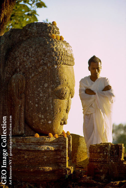A man prays at a Buddha where he has placed an offering of flowers.