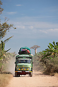 A local loaded transport vehicle driving down a dusty road near Morondava, Madagascar