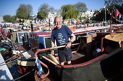 © Licensed to London News Pictures. 07/05/2018. London, UK. A canal boat owner makes adjustments to his canalboat in the early morning sunshine at day three of the Canalway Cavalcade festival takes place in Little Venice, West London on Monday, May 7th 2018. Today is expected to be the hottest May bank holiday Monday on record. Photo credit: Ben Cawthra/LNP