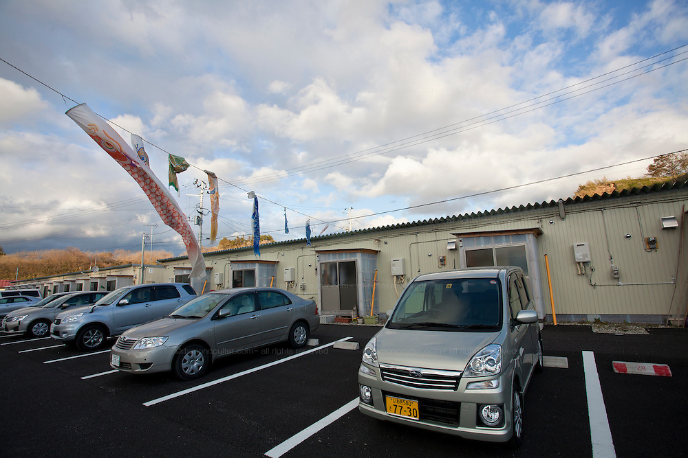 Koinoburi (Carp Flags for the boys festival) floy over the car park of a temporary housing unit on the outskirts of Miharu, Tamura District of Fukushima, Japan, Wednesday May 1st 2013. Many people were moved into temporary housing after the earthquake and tsunami of march 11th 2011 left people homeless due to their houses being flattened in the tsunami or contaminated by radiation from the accident at Fukushima Daichi nuclear power station.