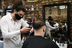 © Licensed to London News Pictures. 12/04/2021. London, UK. A man gets his hair cut in a barbers on Green Lanes in Haringey, north London, which reopens after 4 months of Covid-19 lockdown. Cafes, restaurants, pubs, non-retail business and hairdressers across the UK closed following third national lockdown on 6 January, after a surge of coronavirus infections and hospital admissions across the UK. As restrictions are eased, cafes, restaurants, pubs, non-retail business and hairdressers reopen today.<br /> Photo credit: Dinendra Haria/LNP