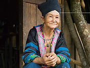 Portrait of a Hmong woman wearing her traditional clothes outside her home, Ban Chalern, Phongsaly province, Lao PDR. The remote and roadless village of Ban Chalern is situated along the Nam Ou river (a tributary of the Mekong) and will be relocated due to the construction of the Nam Ou Cascade Hydropower Project Dam 7. The Nam Ou river connects small riverside villages and provides the rural population with food for fishing. But this river and others like it, that are the lifeline of rural communities and local economies are being blocked, diverted and decimated by dams. The Lao government hopes to transform the country into 'the battery of Southeast Asia' by exporting the power to Thailand and Vietnam.