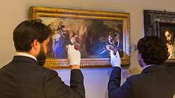 London, July 3rd 2017. Bonhams gallery assistants examine Bartolomé Esteban Murillo's Moses Drawing Water from the Rock, which is estimated to fetch between £60-80,000 in their forthcoming Old Master Paintings sale.