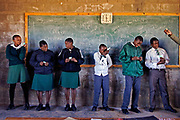 Peace Corps Volunteer Jean Margaritis and Youth Counselor Tsepo Rameane (not in picture), discuss HIV and Aids with Grades 8-10 students at Mahobong Secondary School, in Leribe, Lesotho. Students are taught how to open condoms, how to properly use them and to check expiration dates. The school has 130 students; 60 - 70 per cent of the students are either single or double orphans.