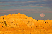 The full moon sets behind a golden ridge along the Conata Basin in Badlands National Park, South Dakota.