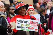 A woman with a banner and a slice of bread at the Bread and Roses Womens March on January 19, 2019 in London, England.  The event was dubbed the Bread and Roses March based on the strikes of the same name by textile workers in Massachusetts in 1912 and Bread and Roses is the title of a poem by American poet James Oppenheim about the strikes.