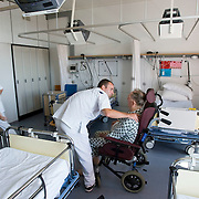 Nederland Rotterdam  31-08-2009 20090831 Foto: David Rozing .Serie over zorgsector, Ikazia Ziekenhuis Rotterdam. Afdeling neurologie, stroke unit, revalidatie oefeningen bejaarde man op zaal. Broeders ondersteunen een patient tijdens oefeningen om opnieuw te leren lopen en brengen hem terug naar zijn rolstoel. De patient heeft een beroerte gehad en daardoor is oa zijn ( grove ) motoriek aangetast, deels verlamd geraakt.  Revalidation old patient, nurses practice walking, supporting him while a makes small steps. Patient has suffered a stroke. .Na een ernstige beroerte wordt u opgenomen in een gespecialiseerde afdeling of een afdeling intensieve zorgen van het ziekenhuis. Na de eerste 24 uur is het nodig om een aangepast revalidatieprogramma te starten. dat kan bestaan in wisselhoudingen en passieve bewegingen van de verlamde lichaamshelft.  .  ..Foto: David Rozing .Holland, The Netherlands, dutch, Pays Bas, Europe, menselijk contact, verpleger, verplegers, verplegend, status.,  oud, oude, op leeftijd, revalidatie, revalideren, revalidation, nursing,steun, steunen, helpen, wheelchair, aanmoedigen, , mobiliteit, niet mobiel zijn, verlamd zijn, niet goed kunnen lopen, ondersteunen,oefening, oefenen, opnieuw leren te,zorgverlener, zorgverleners,zorgverlening,  , cva, ,hersenschade.,zorgverleners,zorgverlening, cognitief, hersenletsel, herseninfarct, hersenbloeding, interactie patient verpleging, tijd hebben voor, hulp, helpen,, nursing, aansterken, handeling, handelingen,ondersteuning,.ronde doen,aandacht hebben voor geven,  menselijk contact ,   aanmoedigen,moral support, blijk van affectie, steuntje in de rug,  steunbetuiging, verpleger, verplegers, verplegend