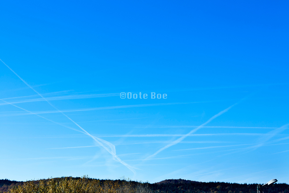 various airplane vapor trails converging and crossing