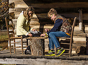 A mother and son play a game of checkers on the porch of an old cabin at Humpback Rocks Mountain Farm, a restored 1890s farmstead open to the public at Milepost 5.8 on the Blue Ridge Parkway, in Virginia, in the Blue Ridge Mountains (a subset of the Appalachian Mountains), USA. In summer, costumed interpreters demonstrate 1890s southern Appalachian mountain life. European settlers of the Appalachian Mountains forged a living from abundant native materials: hickory, chestnut, and oak trees provided nuts for food, logs for building, and tannin for curing hides; and the rocks were used as foundations, chimneys and stone fences. This farm was originally a Land Grant tract dispensed by the Commonwealth of Virginia to induce pioneers to settle; and later it became known as the William J. Carter Farm. For licensing options, please inquire.