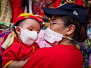 05 FEBRUARY 2019 - BANGKOK, THAILAND: An infant in his mother's arms tries on a traditional style Chinese hat at a Chinese New Year souvenir stand on Yaowarat Road in Bangkok. They were breathing masks because of the air pollution in Bangkok. Chinese New Year celebrations in Bangkok started on February 4, 2019, although the city's official celebration is February 5 - 6. The coming year will be the Year of the Pig in the Chinese zodiac. About 14% of Thais are of Chinese ancestry and Lunar New Year, also called Chinese New Year or Tet is widely celebrated in Chinese communities in Thailand.      PHOTO BY JACK KURTZ