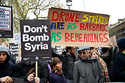 Whitehall November 28th Protest organised by Stop the War against the proposed bombing of Syria. A protester holds a handmade sign saying 'Drone strikes are as barbaric as beheadings'.