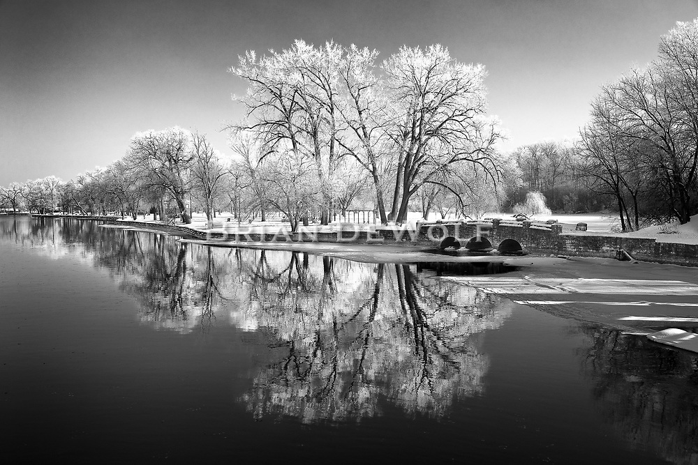 This is an open edition print. Canvas prints have a 2 inch black border so it can be gallery wrapped. The print is made using pigmented inks on museum-grade canvas or watercolor paper. Each print also gets a light coating of lacquer protective spray. Each print is hand signed by Brian DeWolf.   The scene is Island Park in Geneva on the morning of a winter frost in December 2010.  As the reflection in the water indicates, it was a still morning. No wind was blowing.  The sun, weakened by winter solstice, still had the strength to melt the delicate lace before mid-morning.  It was a brief and beautiful moment in time.