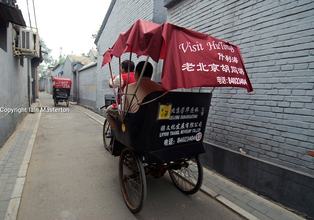 Tourists riding a rickshaw tour of historic hutongs in central Beijing China