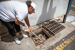 Lisa Hunt clears trash and debris from a storm drain during the Garden Street cleanup.  Residents and volunteers gather for the Garden Street neighborhood cleanup and block Party hosted by E's Garden and Things, Long Path/Garden Street Community Association, and the Economic Development Authority's Enterprise and Commerical Zone Commission.  St. Thomas, USVI.  5 September 2015.  © Aisha-Zakiya Boyd