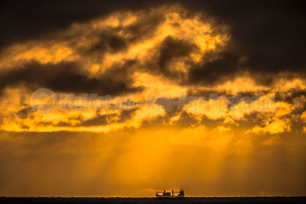 Vessel sailing in a golden horizon   Båt som seiler i en gyllen horisont