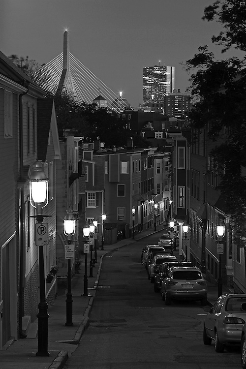 Boston Black and White photography showing a none familiar view of the Boston skyline at twilight including landmarks such as John Hancock building, now known as 200 Clarendon and Leonard P. Zakim Bunker Hill Memorial Bridge. Photograph taken from Pleasant Street in Charlestown, MA near the Bunker Hill Monument, end of the famous Boston Freedom Trail. <br /> <br /> B&W Boston Charlestown photography images are available as museum quality photography prints, canvas prints, acrylic prints or metal prints. Fine art prints may be framed and matted to the individual liking and decorating needs:<br /> <br /> http://juergen-roth.pixels.com/featured/charlestown-view-of-boston-juergen-roth.html<br /> <br /> All Boston Black and White photos are available for digital and print image licensing at www.RothGalleries.com. Please contact me direct with any questions or request.<br /> <br /> Good light and happy photo making!<br /> <br /> My best,<br /> <br /> Juergen<br /> Prints: http://www.rothgalleries.com<br /> Photo Blog: http://whereintheworldisjuergen.blogspot.com<br /> Instagram: https://www.instagram.com/rothgalleries<br /> Twitter: https://twitter.com/naturefineart<br /> Facebook: https://www.facebook.com/naturefineart