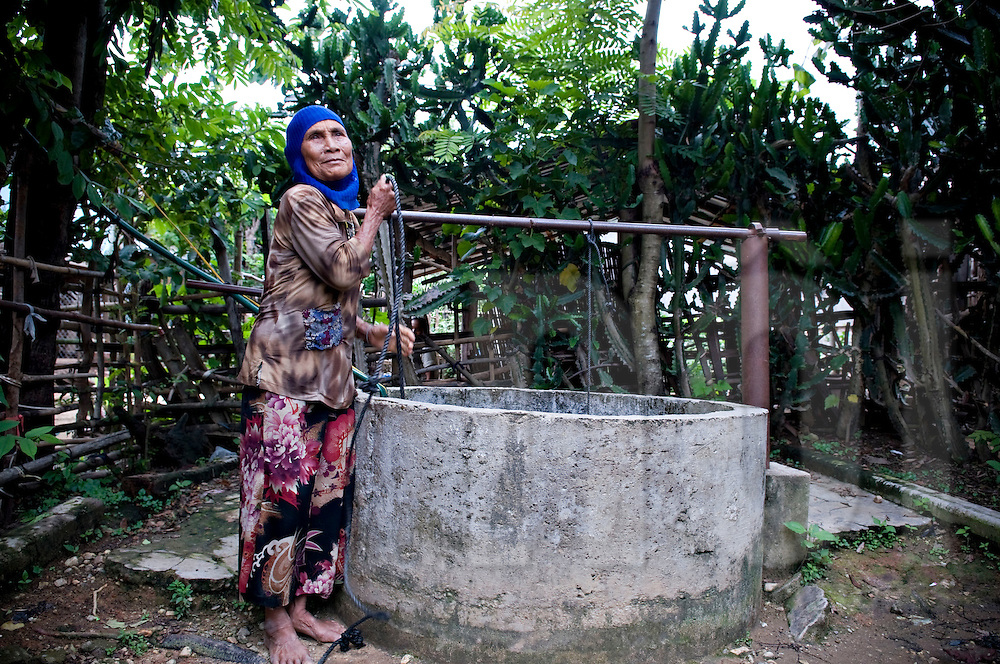 An old woman from Reungao ethnic tribe draws water from a well. Kontum plateau, Pleiku area, Vietnam, Asia