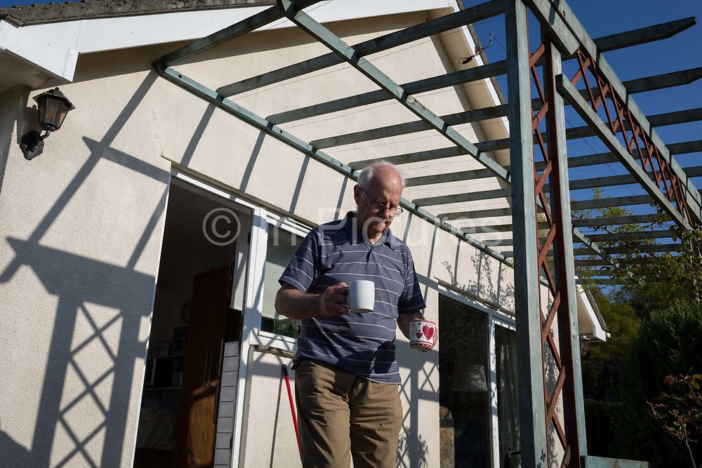 An elderly man of 80 years of age brings two mugs of tea beneath the shadows of a patio shelter, 5th May 2018, in Wrington, North Somerset, England.