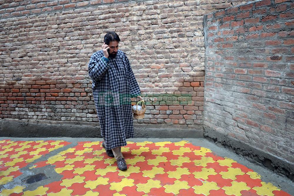 A Kashmiri man walks briskly holding firepot in his hands amid snowfall in Srinagar, the summer capital of Indian controlled Kashmir. Kashmir witnessed its first snowfall.