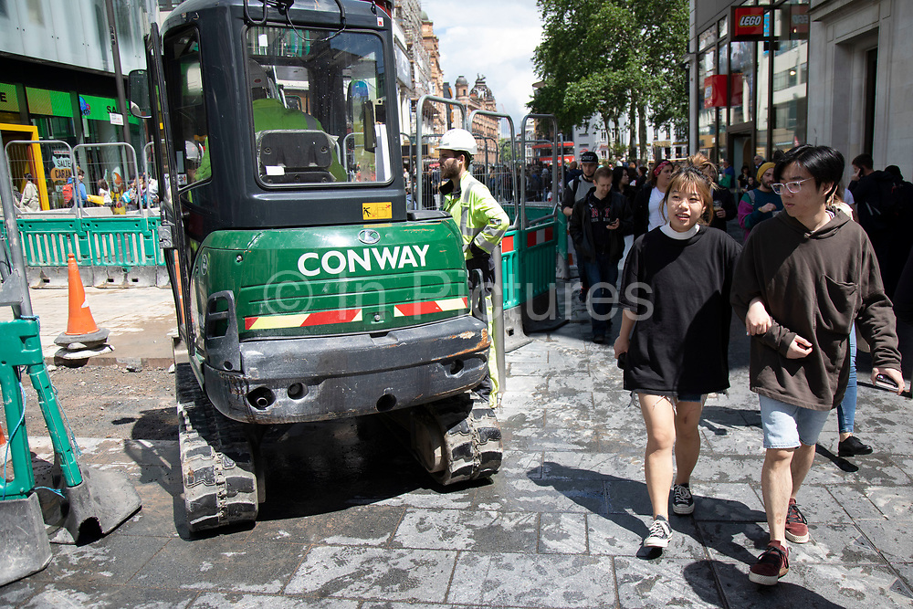 Tourists pass as a small digger does some ground work on the pavement in Leicester Square in London, England, United Kingdom.