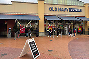 People stand in line outside the Old Navy outlet store the day before Christmas at the Citadel Outlets amid the global coronavirus COVID-19 pandemic, Thursday, Dec. 24, 2020, in Los Angeles.