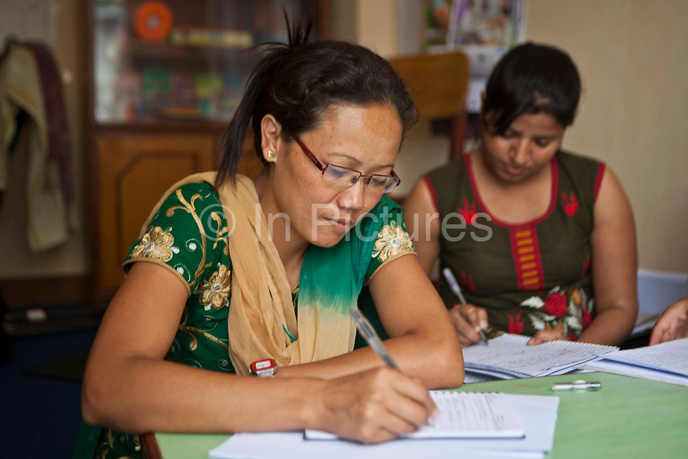 Nepalese female staff sit and write notes during a meeting in the Voice of Children centre in Kankeshori area of Kathmandu, Nepal.  The not-for-profit organisation supports street children and those who are at risk of sexual abuse through educational and vocational training opportunities, health services and psychosocial counseling.