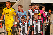 Seny Dieng of Dundee FC and Paul McGinn (C) of St Mirren lead out their respective teams  ahead of the Ladbrokes Scottish Premiership match between St Mirren and Dundee at the Paisley 2021 Stadium, St Mirren, Scotland on 30 March 2019.