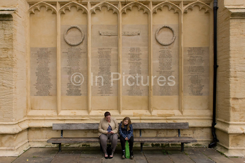 Locals from Cirencester in the county of Gloucestershire sit below the first world war memorial on St John Baptist <br /> church wall in the city centre. A mother and child sit on a bench below the names of those local men lost in the first war (AD1914-18) - the 200 names tell a story of the lost generation of youth, now replaced by the modern Brit, unused to self-sacrifice and loss on an unimaginable scale. The church is medieval, renowned for its perpendicular porch, fan vaults and merchants' tombs. The chancel is the oldest part of the church. Construction started around 1115.