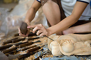 Village of Du Du specialized in manufacturing of woodcarving. Here a vietnamese women working on a buddha