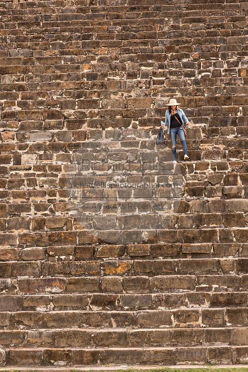 A tourists walks down the steps of the south platform of Monte Albán pre-Columbian archaeological site in the Santa Cruz Xoxocotlán, Oaxaca, Mexico.