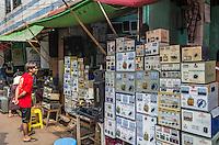 YANGON, MYANMAR - CIRCA DECEMBER 2013: Merchant selling transformers in the Yangon street market.