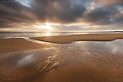 Sunset and clouds over wide sandy beach at low tide, at Rhosneigr, West Anglesey.