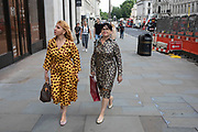 Two fashionably dressed women wearing stylish patterned dresses in London, United Kingdom.