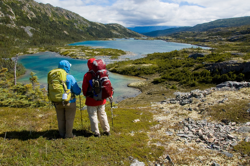 Backpackers survey the beautiful torquoise lakes along the Chilkoot Trail. PLEASE CONTACT US FOR DIGITAL DOWNLOAD AND PRICING.