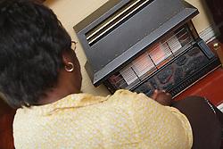 Old black lady keeping warm by gas fire