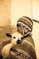 A quechua boy poses with his lamb in Cusco, Peru